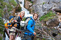 Austria, Steiermark, Ramsau, Silberkarklamm, Young couple walking on rope, looking away