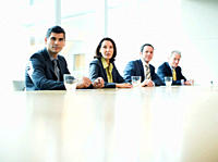 Business people sitting in a row at conference table