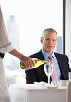 Waitress pouring white wine for businessman in restaurant