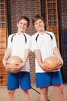 Germany, Emmering, Boys 12_14 holding ball and smiling, portrait