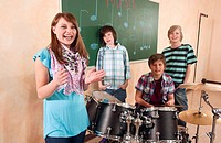 Germany, Emmering, Girl smiling with boys in background playing drum, portrait