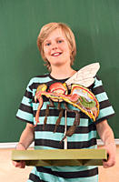 Germany, Emmering, Boy12_13 holding and fly model, smiling, portrait