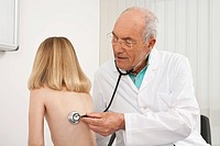 Germany, Munich, Doctor hearing heartbeat of girl 8_9 with stethoscope