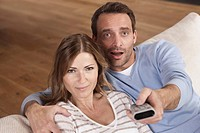 Germany, Couple sitting on couch with man holding remote control, portrait