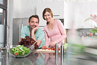 Germany, Couple preparing salad in kitchen, smiling, portrait
