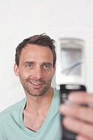 Germany, Man photographing himself with cell phone, smiling
