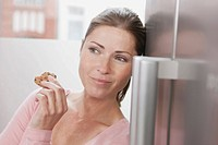 Germany, Close up of woman eating cookie in kitchen