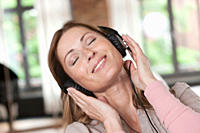 Germany, Close up of woman listening music, smiling