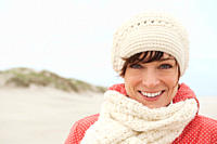 Germany, St Peter_Ording, North sea, Woman having fun in sand dunes, smiling, portrait