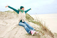 Germany, St Peter_Ording, North sea, Woman with arms up and having fun in sand dunes, smiling