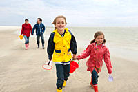 Germany, St. Peter_Ording, North Sea, Children 6_9 with parents walking on beach