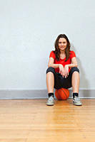 Germany, Berlin, Young woman sitting on basketball in school gym, smiling