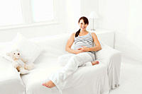 Pregnant woman sitting on sofa