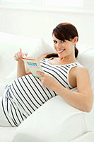 Pregnant woman with baby name book
