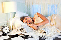 Young woman lying amongst pillow feathers in small room