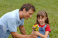 Father giving flowers to daughter, smiling