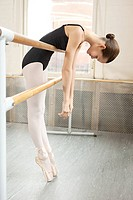 Ballerina leaning over barre