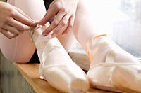 Girl tying ballet shoes