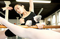 Ballerinas stretching at barre