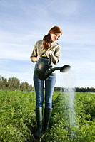 Woman watering crop in field with watering can (thumbnail)