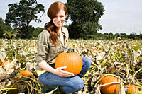 Young woman holding pumpkin