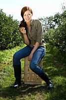 Young woman eating apple in orchard