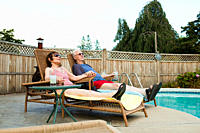 Senior couple relaxing by swimming pool (thumbnail)