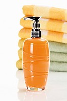 Soap in soap dispenser with stack of towels in background