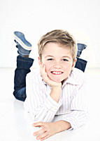 Boy 8_9 lying with hand on chin, smiling