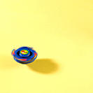 Pegtop spinner spinning on Yellow Background