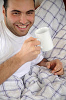 Young man drinking coffee in bed