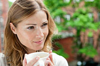 Germany, Woman holding coffee cup and looking away, smiling