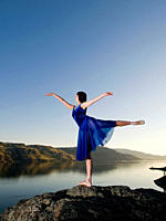 A beautiful young lady practises dance over Kamloops lake at sunset, Kamloops, British Columbia, Canada.