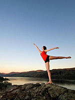 A young women practises her dance moves over Kamloops lake on a stunning evening, Kamloops, British Columbia, Canada