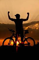 Germany, Lower Bavaria, Biker with bike at sunset
