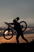 Germany, Lower Bavaria, Biker carrying bike and walking at sunset