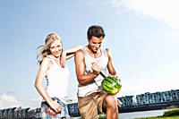 Germany, Cologne, Man cutting watermelon, woman smiling
