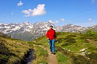 Young woman hiking on a narrow trail in the high mountains, Valais Alps, Valais, Switzerland