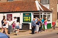 People outside Kens traditional fish and chips chip shop restaurant in Wroxham , Norfolk , England , Great Britain , Uk