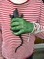 A person with a green hand holding a toy rat