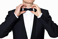 A man wearing a tuxedo adjusting his bow tie