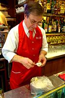 Barista filling a cannolo pastry with sweet ricotta cheese in a cafe in Palermo Sicily Italy Europe