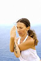 Attractive young woman, artist Lena Tancredi, practicing yoga in front of the Mediterranean Sea, Ibiza, Spain