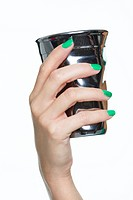 Close-up of woman's hand holding silver cup (thumbnail)