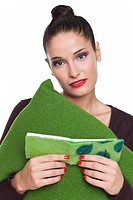 Young woman holding cushion and noteboook
