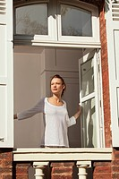 Young woman opening window (thumbnail)