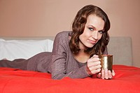 Young woman holding a cup in bed
