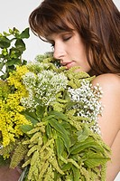 Young woman covering breast with flowers (thumbnail)