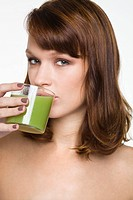 Young woman drinking glass of wheatgrass juice