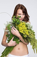 Young woman covering breast with flowers